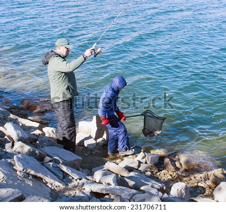 Father and son catch trout in the lake. Adult fish caught, and the child helped pull her out of a net water - stock photo