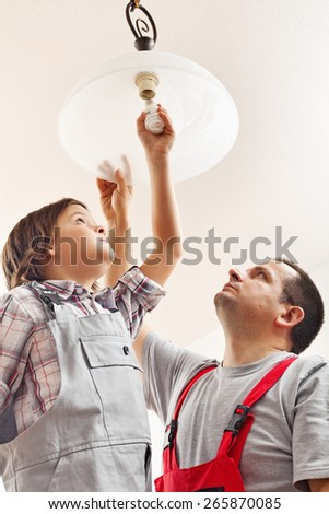 Father and son changing lightbulb in a ceiling lamp together - stock photo