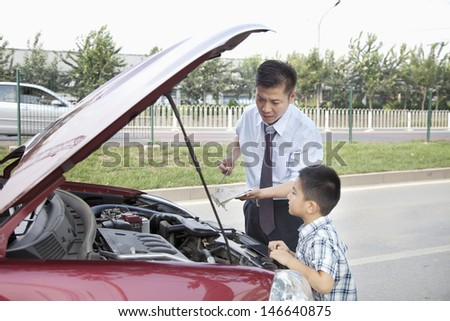 Father and Son Check the Oil on Their Car - stock photo