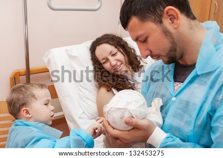 Father and son come to visit mom in the maternity ward - stock photo