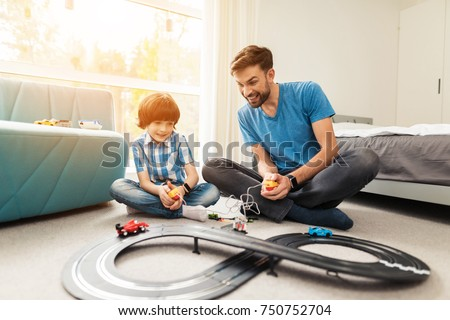 Nice Father And Son Compete In Races With Childrenu0027s Cars. They Play Together On  The Floor