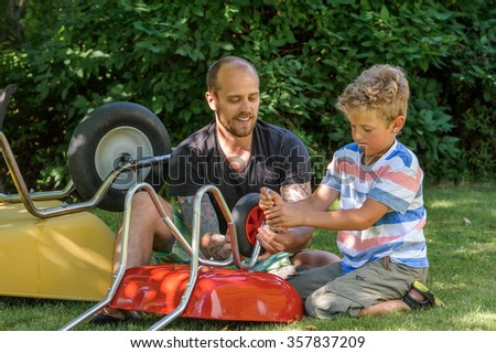 Father and son construct or repair a child's wheelbarrow together. They are sitting on grass. In the background there's an adult wheelbarrow. Dappled sunlight on the grass. The man has tattoos. - stock photo
