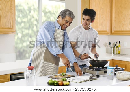 Father and son cooking food in the kitchen - stock photo