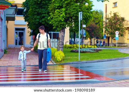 father and son crossing the city street on crosswalk - stock photo