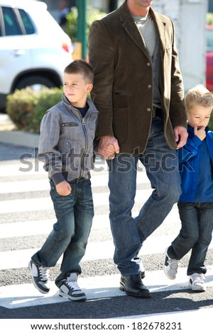 Father and son crossing the cross walk - stock photo
