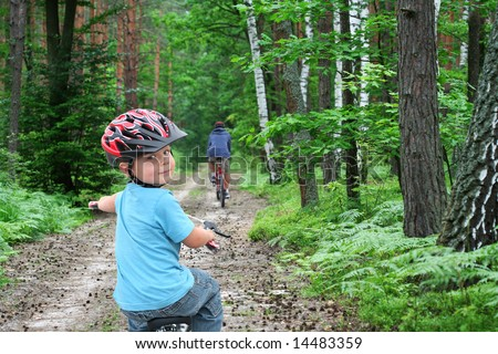 Father and son cycling on a green forest path - stock photo