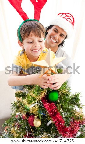 Father and son decorating a Christmas tree at home - stock photo