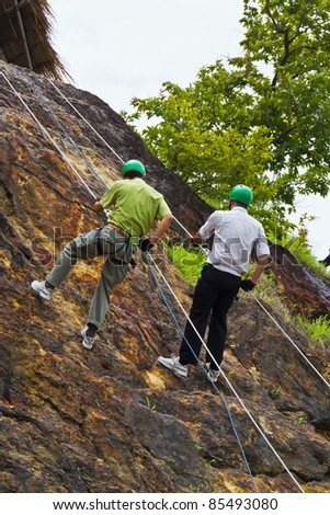Father and son do cliff abseiling recreation in Nakorn Nayok, Thailand