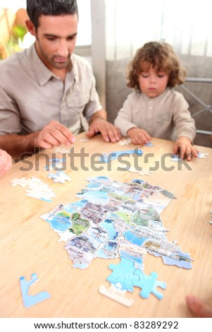 Father and son doing jigsaw puzzle