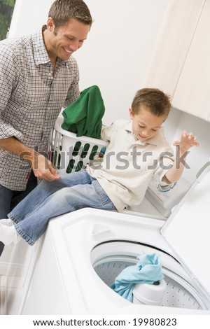 Father And Son Doing Laundry - stock photo