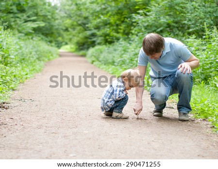 Father and son draw on the land - stock photo