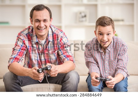 Father and son dressed casual having fun at home while playing computer games. - stock photo