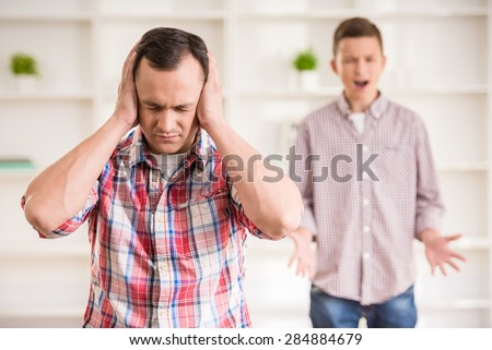 Father and son dressed casual having quarrel at home. - stock photo