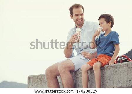 Father and son eating ice cream together at the beach on vacation having fun with melting mess - stock photo