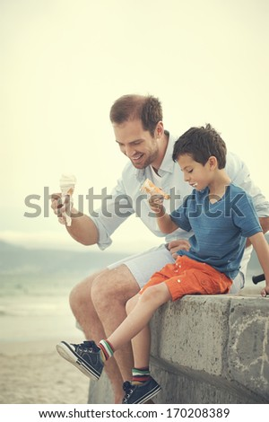 Father and son eating ice-cream together at the beach on vacation having fun with melting mess - stock photo