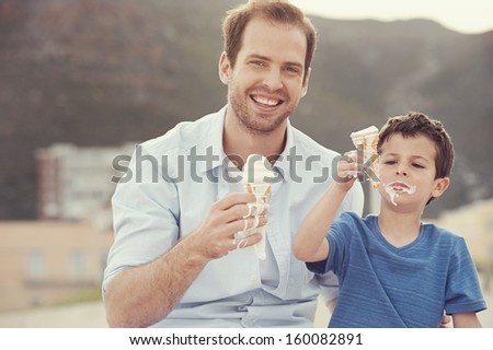 Father and son eating icecream together at the beach on vacation having fun with melting mess - stock photo