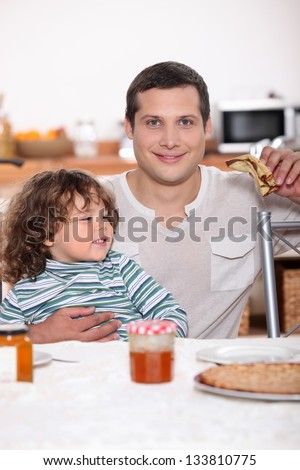 Father and son eating pancakes - stock photo
