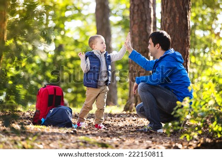 Father and son enjoying a walk in the forest - stock photo