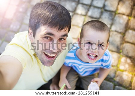 Father and son enjoying ice cream outside in a park - stock photo