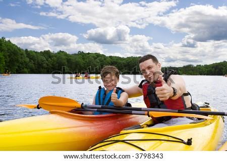 Father and son enjoying kayaking - stock photo
