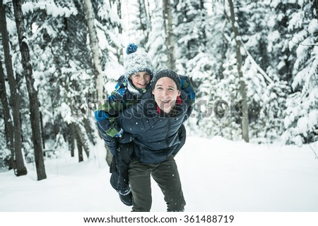 Father and son enjoying snow at daytime - stock photo