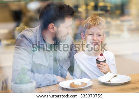 father and son enjoying time together in cafe eating desserts, through the window