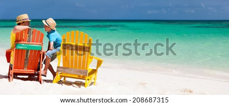 Father and son family sitting on colorful wooden chairs at tropical beach enjoying summer vacation panorama perfect for banners - stock photo