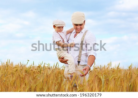 father and son, farmers on wheat field - stock photo