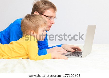 Father and son. Father and son looking at computer monitor  - stock photo