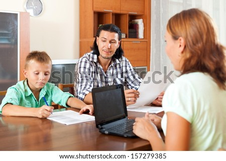 Father and son filling questionnaire for employee of the bank