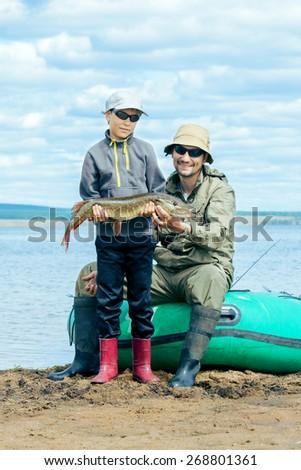 Father and son fish at a boat. Lake Eravna, Russia - stock photo