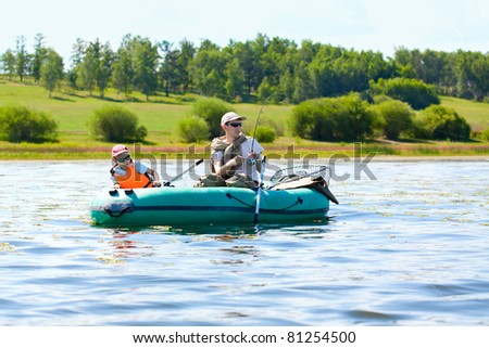 Father and son fish in a boat - stock photo