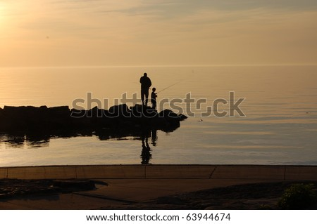 Father and son fish off pier on a summer evening/Evening Fishing/ Finding time together - stock photo