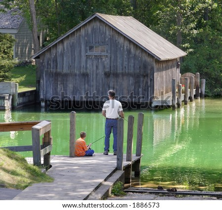 Father and son fish together - stock photo