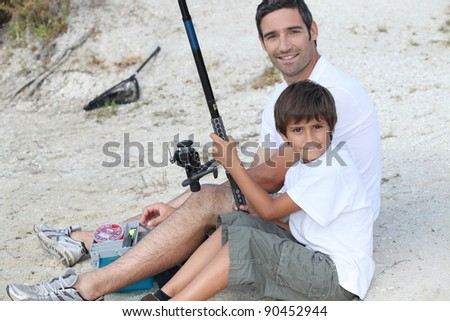 father and son fishing at riverbank - stock photo