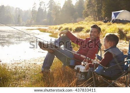 Father and son fishing by a lake, dad looks to camera - stock photo