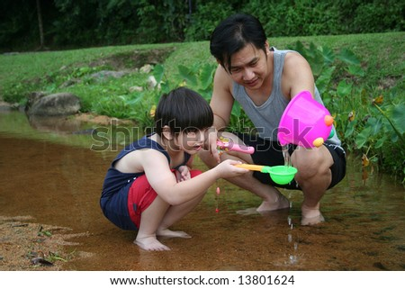 Father and son fishing by the river in the park - stock photo