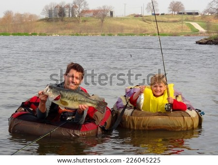 Father and son fishing - in float tubes or belly boat with a big Largemouth Bass and small drum fish - stock photo