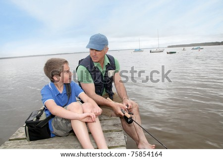 Father and son fishing in lake - stock photo