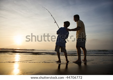 Father and son fishing in ocean surf at sunset. - stock photo