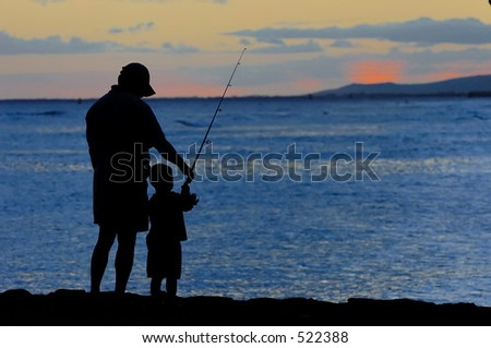 Father and son fishing just after sunset. - stock photo