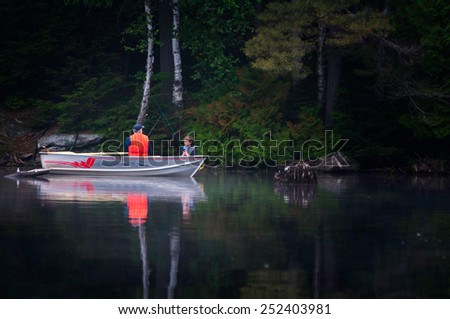 father and son fishing on a lake in a boat on a misty summer morning - stock photo