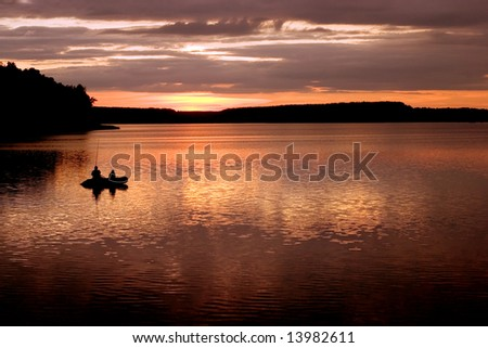 Father and son fishing on rural lake at sunset