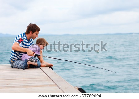 Father and son fishing together by the ocean - stock photo