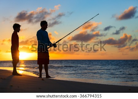 Father and son fishing together in ocean from beach on sunset