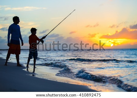 Father and son fishing together in ocean from beach on sunset - stock photo