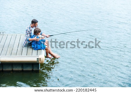Father and son fishing. Top view of father and son fishing together on quayside - stock photo