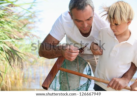 Father and son fishing with net - stock photo