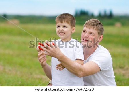 Father and son fly a kite together in summer field - stock photo