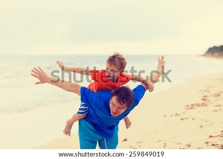 father and son flying at the beach, family fun - stock photo